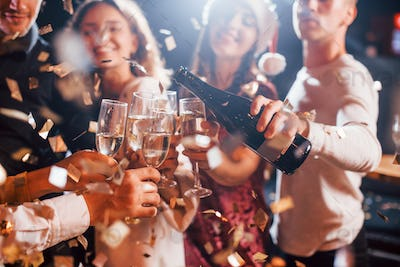 Group of cheerful friends celebrating new year indoors with drinks in hands