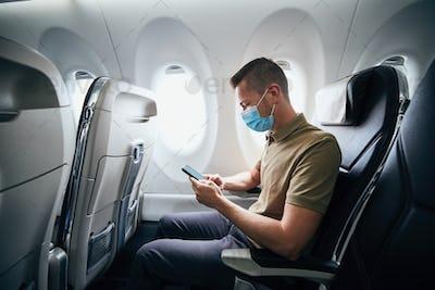 Man wearing face mask inside airplane