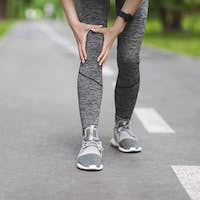 Knee Trauma. Unrecognizable Woman Jogger Hut Her Leg During Running Outdoors
