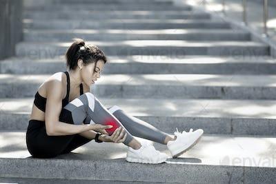 Sporty black girl rubbing injured during exercising leg