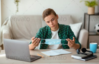 Pensive teen guy holding protective mask, studying at home