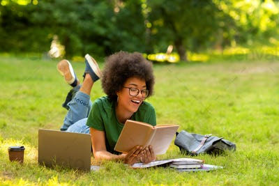 Cheerful African Student Girl Reading Books Outdoors, Lying On Lawn In Park