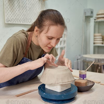 Delight female apprentice working on pottery bowl in workshop