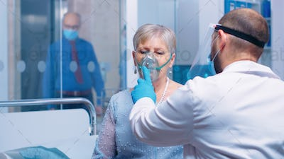Doctor in mask helping old lady to breathe