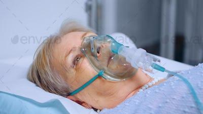 Senior woman breathing slowly with oxygen mask
