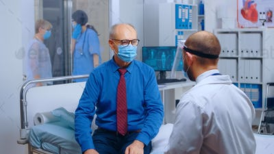 Senior patient wearing mask at doctor appointment