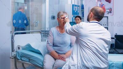 Measuring old senior woman temperature