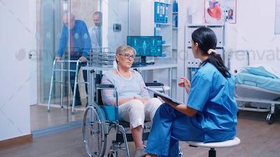 Nurse talking with senior woman in wheelchair