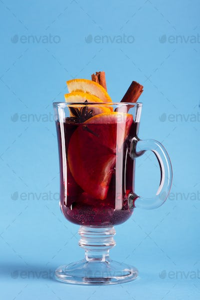 Mulled wine with slice of orange and spices on a blue background