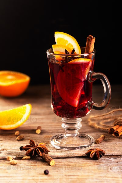 Mulled wine with slice of orange and spices on a wooden background. Dark and moody