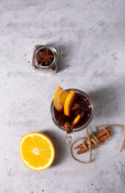 Mulled wine with slice of orange and spices on a concrete background