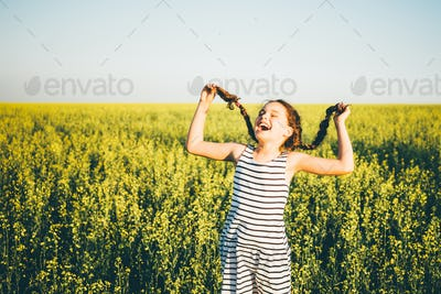girl playing in the rape fields at the sunset time.