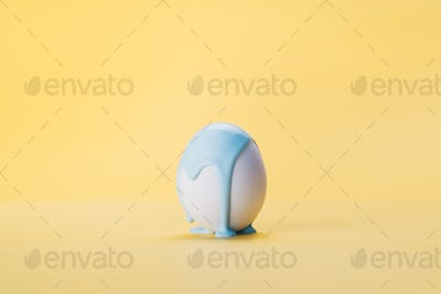 Multi-colored paint slow flowing on white egg howering in air,