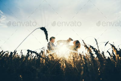 Couple with dog having fun with hay stack