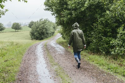 Woman walking down dirt road in rain