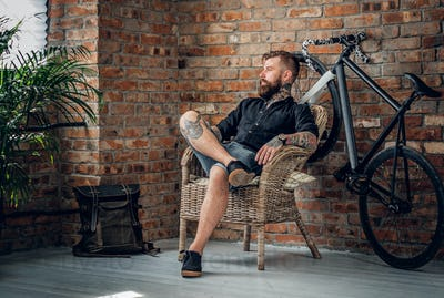 A man sits on a chair in a room with single speed bicycle on bac