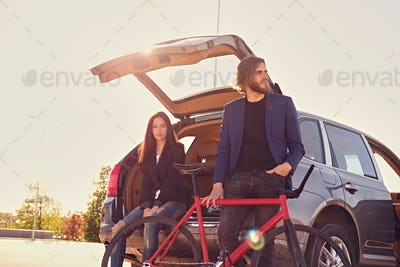 Couple with single speed bicycle near the car with open trunk.