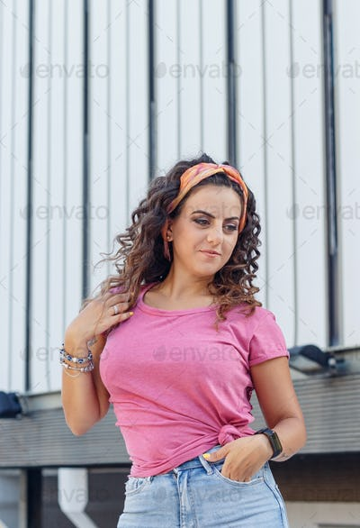 Place it - Young women wearing t-shirt and jeans stay on the street