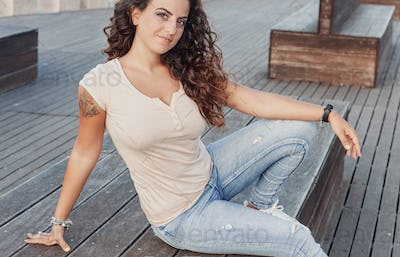 Young women wearing t-shirt and jeans sits on the wooden bench
