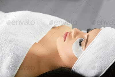 Portrait of girl lying during salon lashes extension procedure
