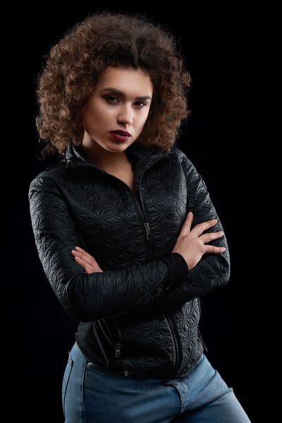 Confident curly girl wearing black jacket and blue jeans