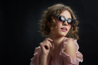 Curly girl wearing fashionable sunglasses