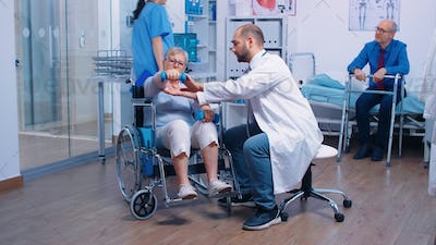 Doctor helping old woman in wheelchair
