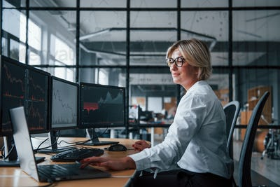 Female stockbroker in formal clothes works in the office with financial market
