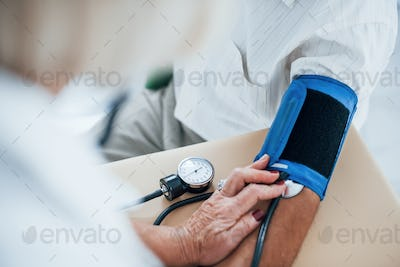 Close up view. Female doctor uses tonometer to make blood pressure measuring to senior man