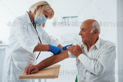 Female doctor injecting senior male patient with syringe in the clinic