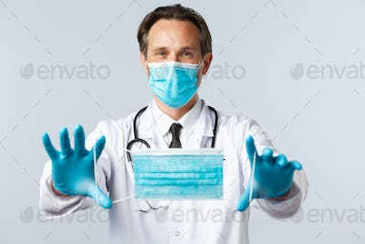 Covid-19, virus, healthcare workers and vaccination concept. Doctor in PPE extend hands and give