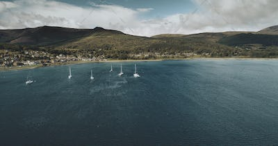 Scotland's sailboats ocean seascape aerial view in coastal water of Brodick Bay. Ships and boats