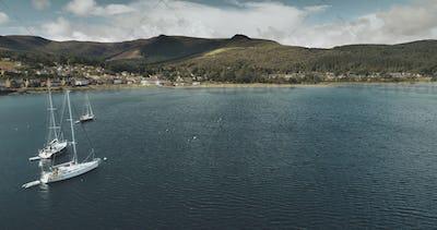 Scotland's ocean coast sailboats aerial view in coastal water near Brodick village, Arran Island