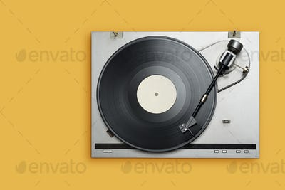 Vinyl player with long play or LP record on yellow background.