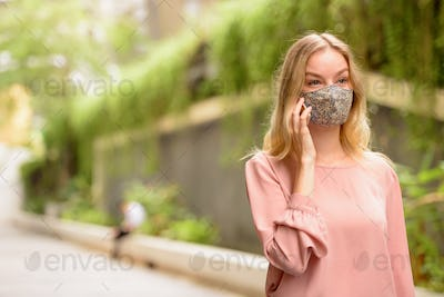 Young blonde woman with mask talking on the phone in the city with nature