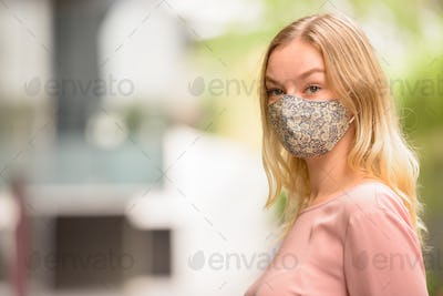 Face of young blonde woman with mask thinking in the city streets with nature