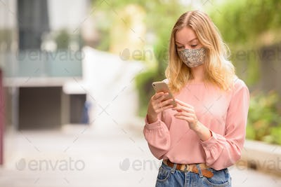 Young blonde woman with mask using phone in the city with nature