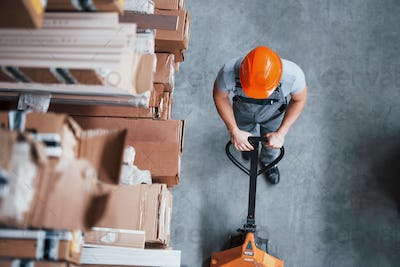 Top view of male worker in warehouse with pallet truck