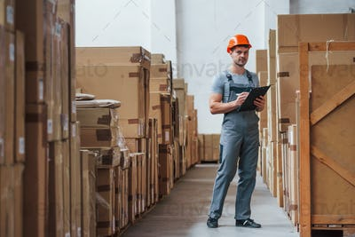 Young male worker in uniform is in the warehouse with notepad and pen