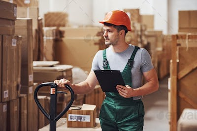 Young male worker in uniform is in the warehouse with notepad and pallet truck