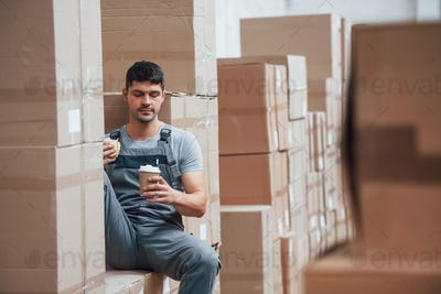 Storage worker sits and have a break. Eats sandwitch and drinks coffee