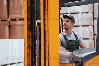 Young worker in unifrom sits in the forklift in the warehouse