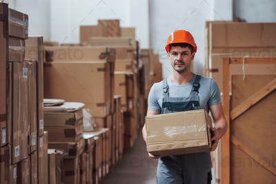 Young male worker in uniform is in the warehouse with box in hands