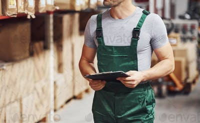 Storage worker in green colored uniform and notepad in hands checks production