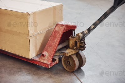 Close up view of dirty red pallet truck with paper box on it