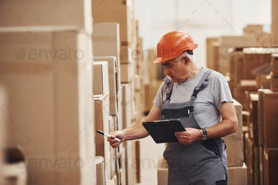 Senior storage worker in uniform and notepad in hands checks production