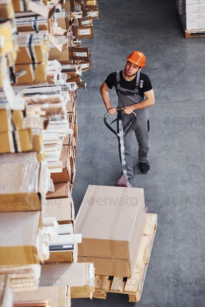 Top view of young male worker in uniform that is in the warehouse pushing pallet truck