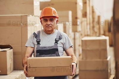 Portrait of senior storage worker in warehouse in uniform and hard hat