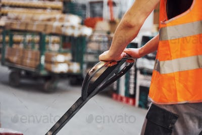 Young male worker in uniform is in the warehouse pushing pallet truck