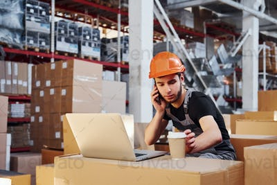 Young storage worker talks by the phone and sitting near his laptop and cup of drink